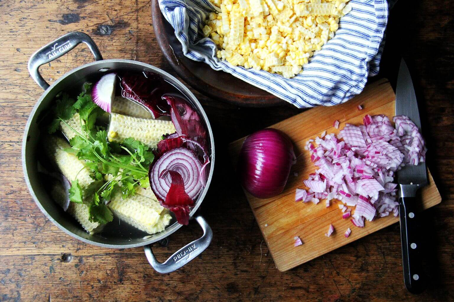 A board with a pot filled with stock ingredients, diced red onion, and stripped corn.
