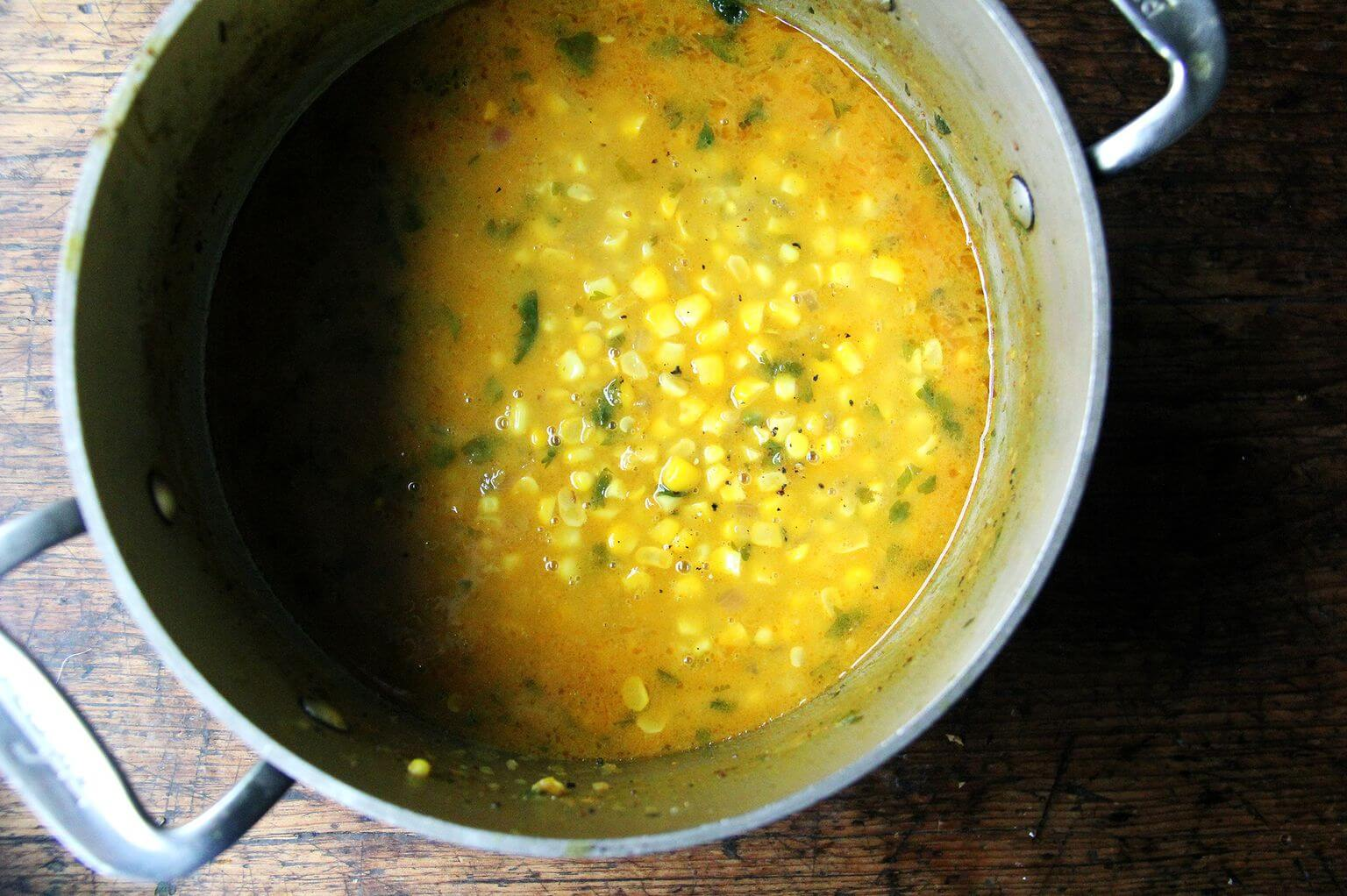 A pot filled with curried coconut corn soup.