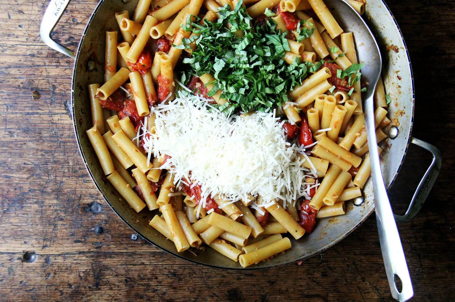 A large skillet with ziti, parmesan, and basil.