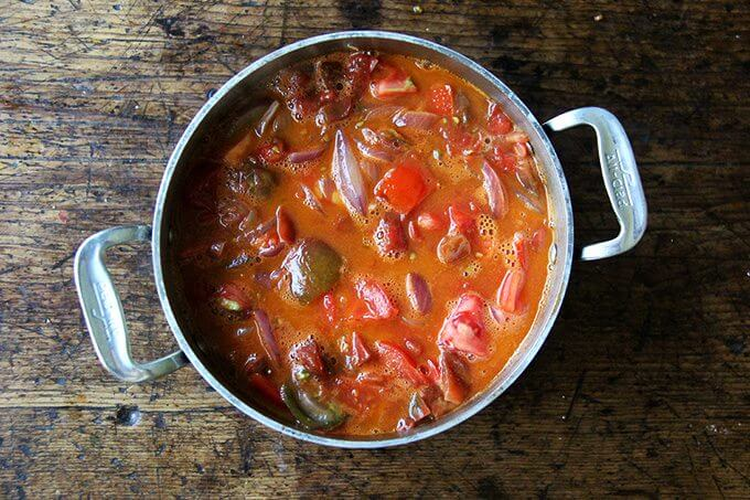 A pot of tomatoes simmering with onions and butter.