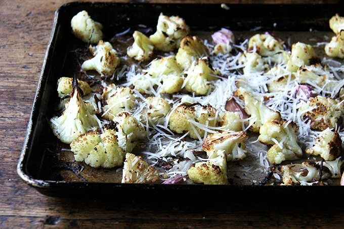 Oven-roasted cauliflower florets on a sheet pan sprinkled with parmesan.
