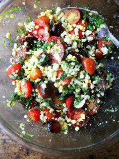 A bowl of raw corn salad with tomatoes, feta, and basil.