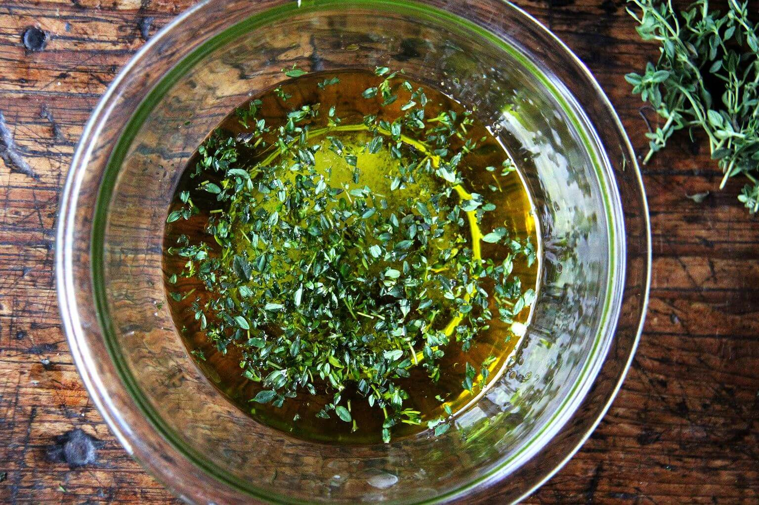 A bowl of olive oil, white balsamic vinegar, and thyme.
