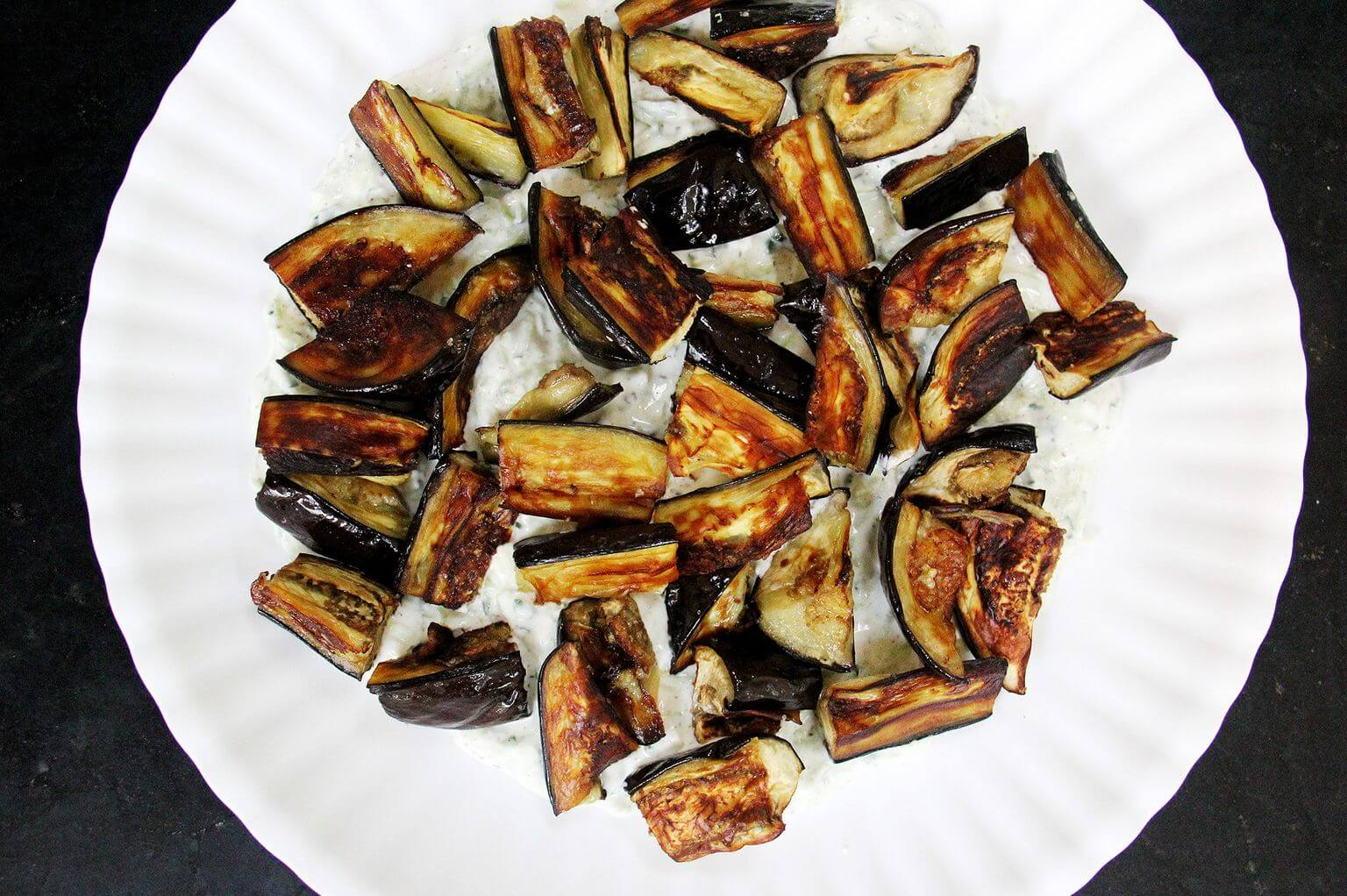 A platter with tzatziki smear and roasted eggplant.