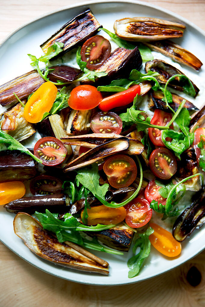 A plate of roasted eggplant salad with tzatziki and tomatoes.