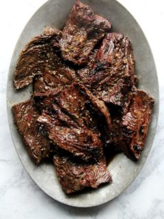 A platter of grilled hanger steak, resting.