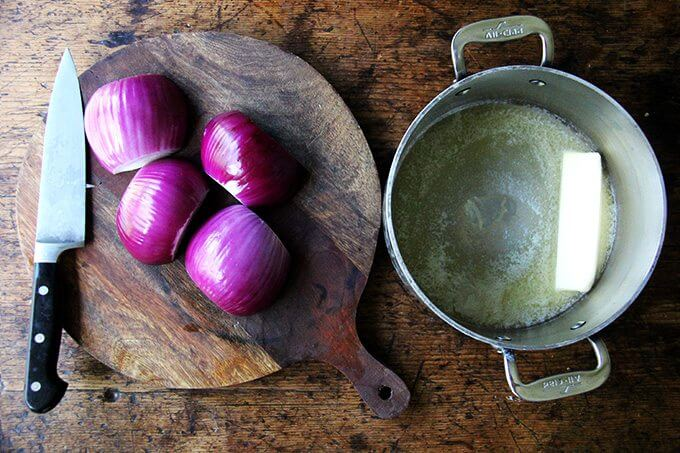 A board of halved onions aside a pot with a stick of butter in it.
