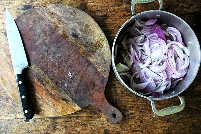 A board aside a pot with a stick of butter in it and 2 sliced onions.