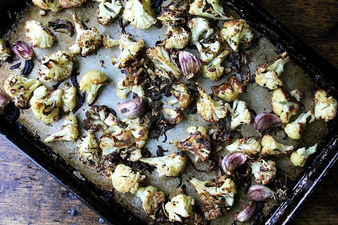 Oven-roasted cauliflower florets with parmesan and garlic on a sheet pan.
