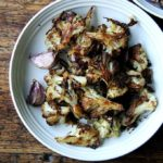 A plate of oven-roasted cauliflower florets with parmesan.