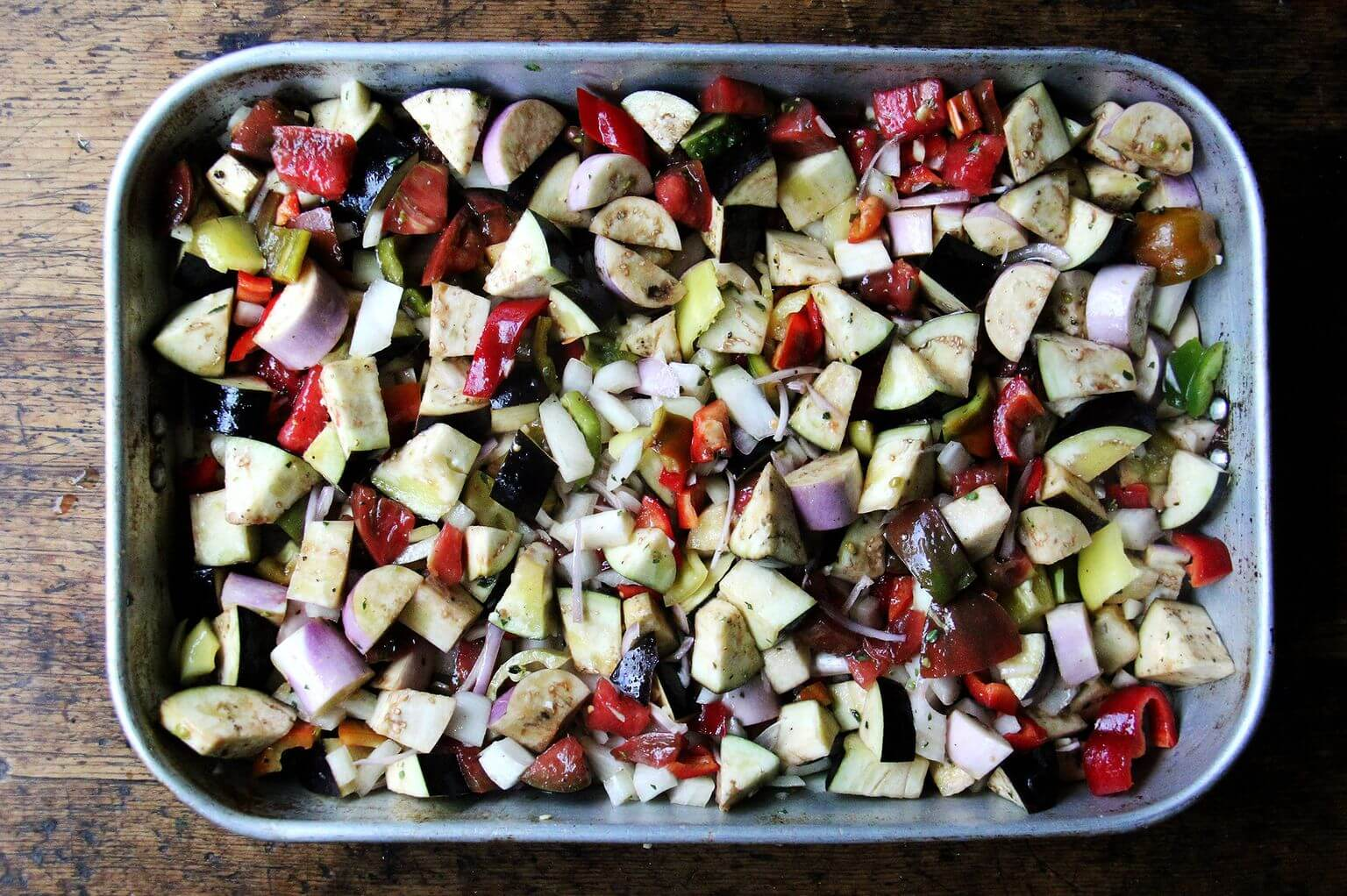 A roasting pan filled with raw, chopped vegetables.
