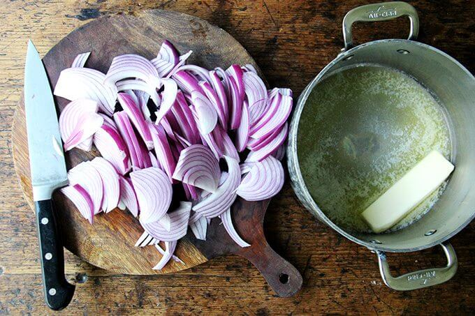A board of sliced onions aside a pot with a stick of butter in it.