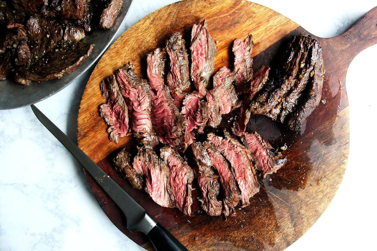 Sliced hanger steak on a cutting board.