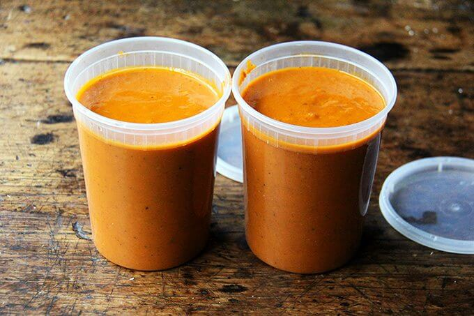 Two quart containers filled with tomato sauce.