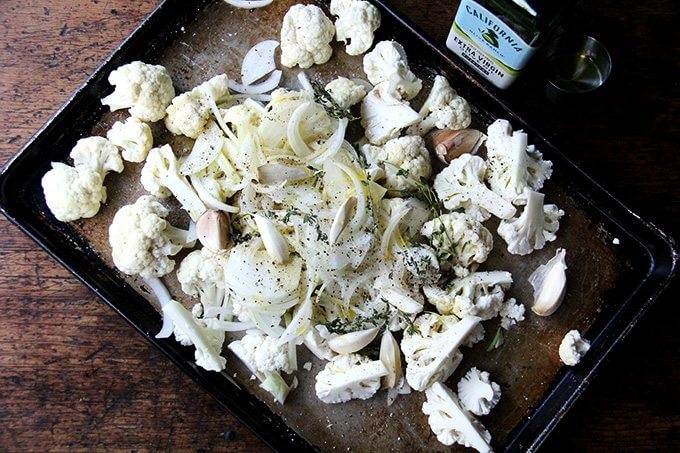 A sheet pan of cauliflower, onions, garlic, and thyme, dressed with olive oil, salt and pepper.