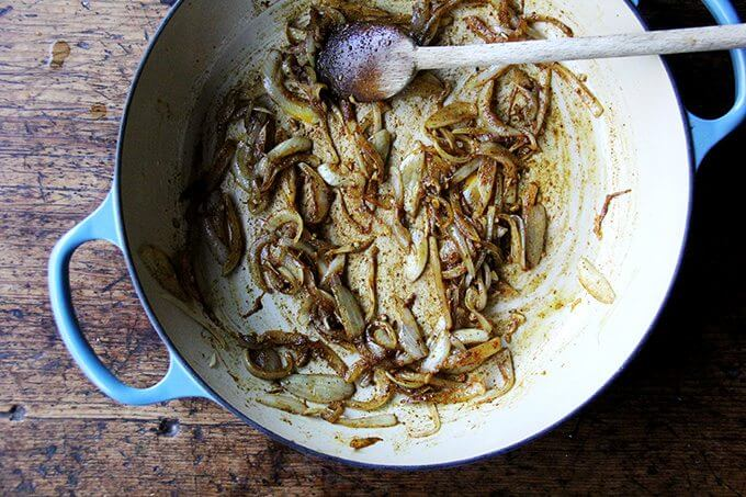 A Le Creuset braiser filled with sautéed onions and ras-el-hanout.