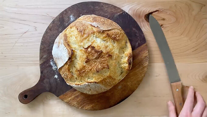A baked loaf of sourdough bread on a cutting board.
