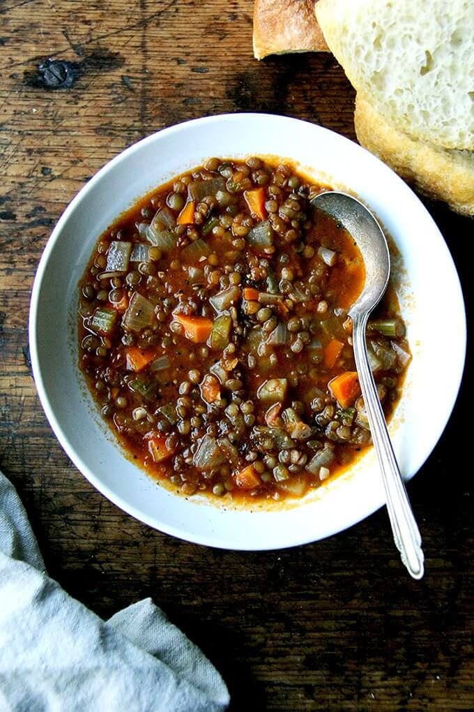 To make this vegan lentil soup, throw everything into a pot and simmer it for one hour. This soup has a nice, vinegary bite and gets better by the day. Soup + bread: what more do we need? // alexandracooks.com