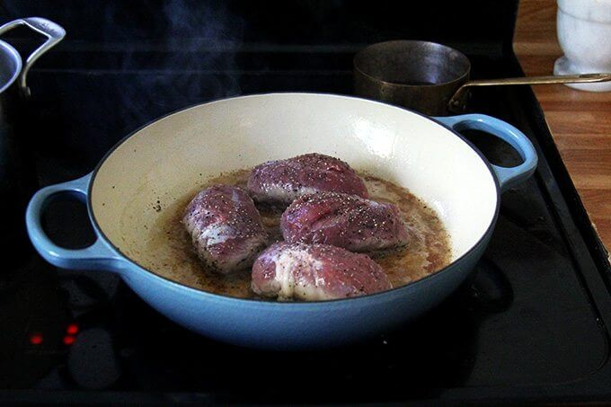 Four duck breasts cooking in a large Le Creuset braiser, stovetop.