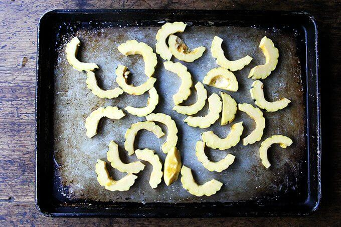 Sliced, raw delicata squash on a sheet pan.