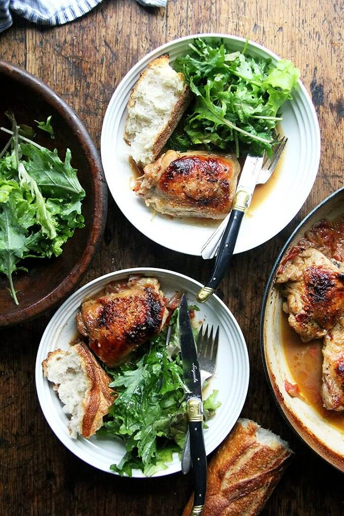 Overhead shot of two dinner plates filled with one-pot chicken with sherry and sherry vinegar sauce, bread, and salad.