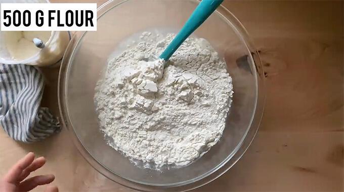 A bowl holding water, salt, flour, and sourdough starter.