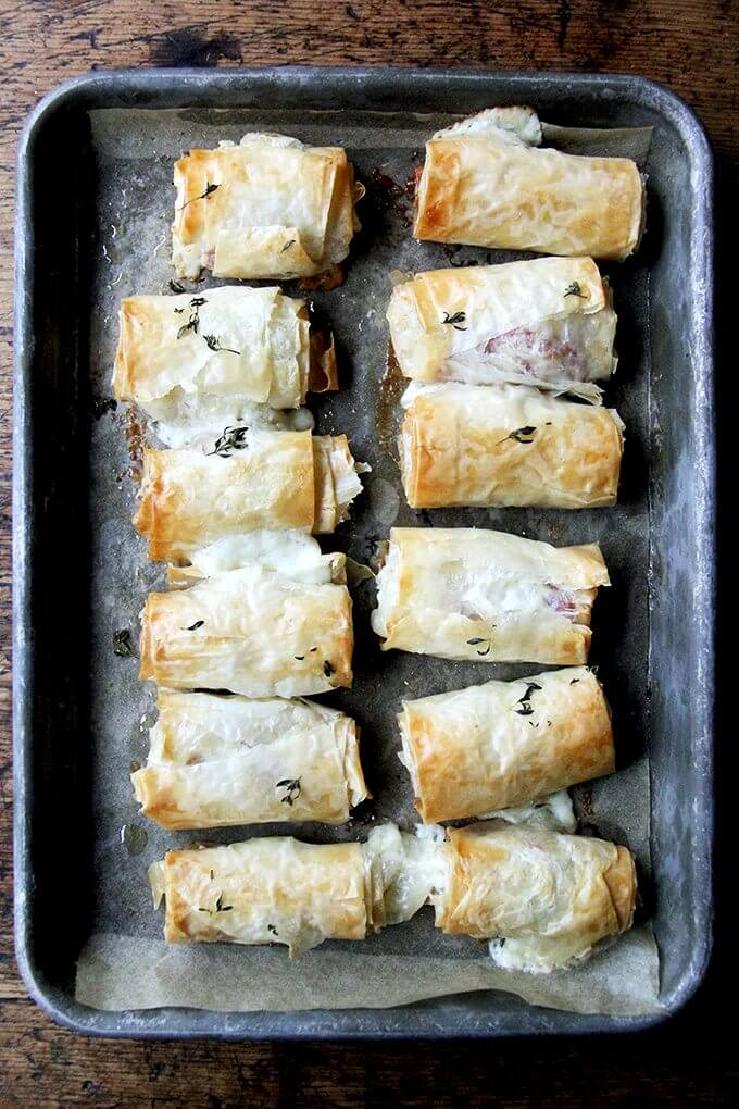 Just-baked salami and provolone phyllo rolls on a platter.