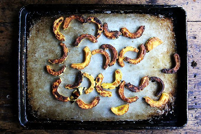 Roasted delicata squash on a sheet pan.