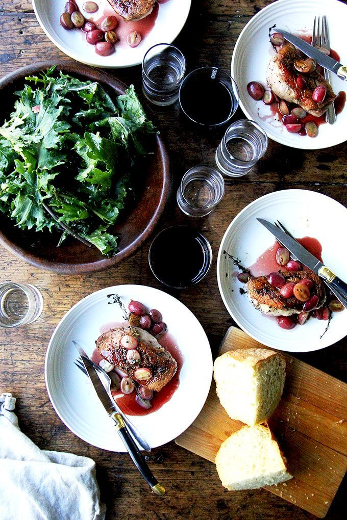 Overhead shot of a table set with 4 plates of duck breast, salad, bread, wine, and water.
