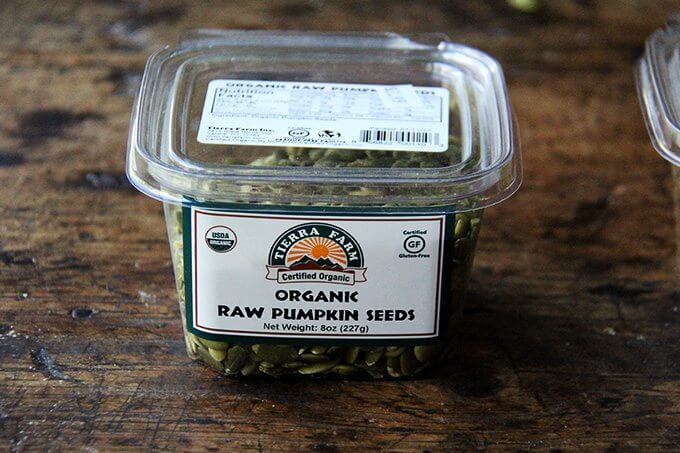 A container of organic, raw, pumpkin seeds.