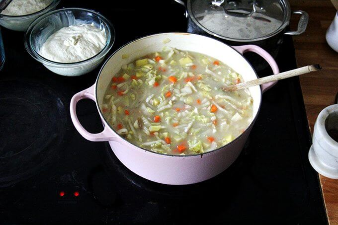 An overhead shot of a stovetop holding a large pot of cabbage soup and two bowls of rising bread dough.