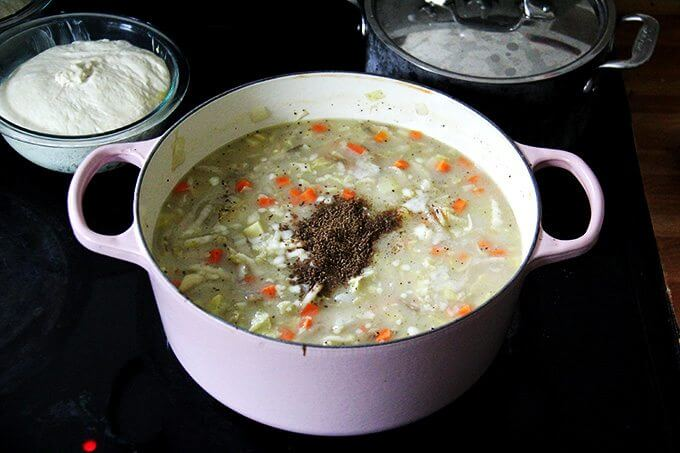 A large pot of vegetarian cabbage soup simmering on the stovetop with caraway added.