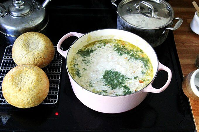 A large pot of vegetarian cabbage soup with heavy cream and dill added aside two loaves of homemade bread.