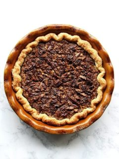 An overhead shot of a slice of no corn syrup bourbon pecan pie on a plate.