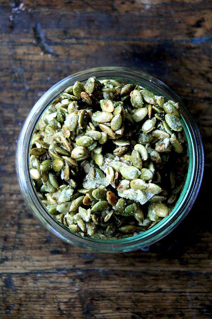A jar of sweet and salty candied pumpkin seeds.