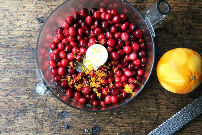 A food processor filled with cranberries and orange zest.