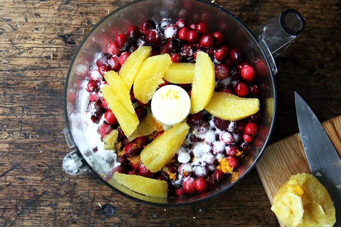 A food processor filled with cranberries, sugar, orange zest, and orange slices.