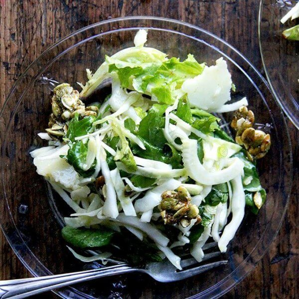 Two plates of a fall salad with cabbage, fennel, greens, and candied pepitas.
