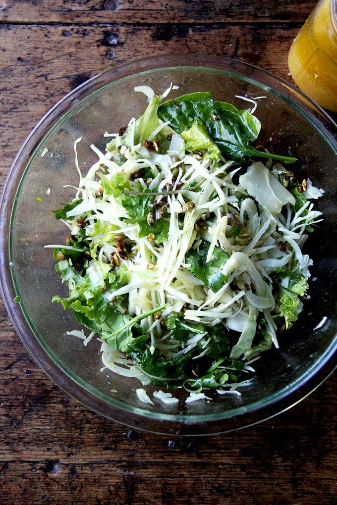 A large bowl filled with fall salad tossed with dressing.