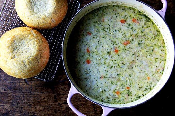 An overhead shot of a large pot of vegetarian cabbage soup aside two loaves of homemade peasant bread.
