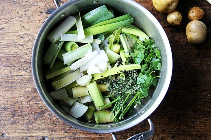 A pot of vegetable stock on a table next to a few potatoes.