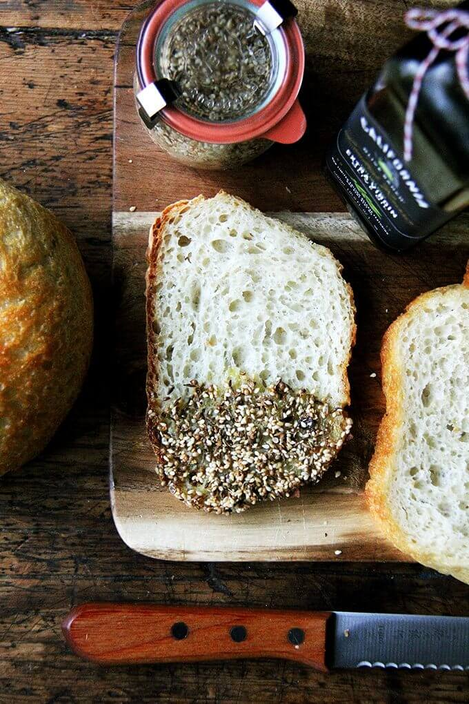 A board with sliced bread dipped in olive oil and dukkah.