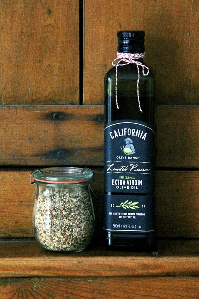 A bottle of California Olive Ranch olive oil aside a jar of homemade dukkah.