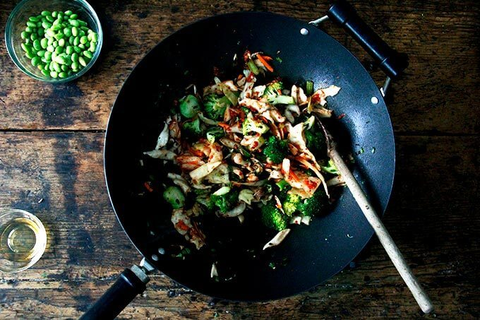 A wok filled with broccoli, shiitakes, and kimchi.