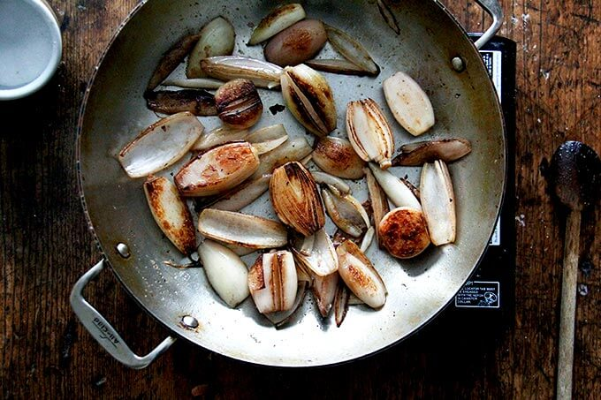 Browned shallots in a skillet.