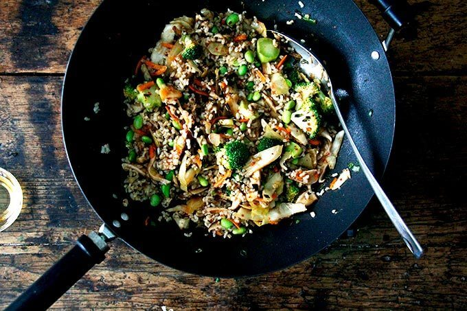 A wok filled with broccoli, shiitakes, kimchi, rice, and edamame.