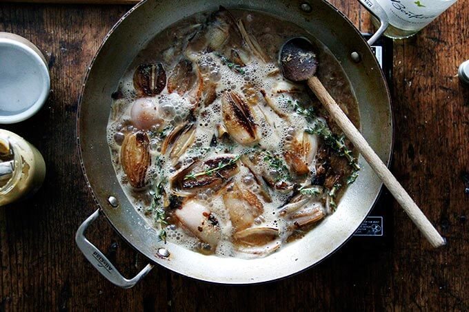 Shallots in a skillet with white wine and thyme.