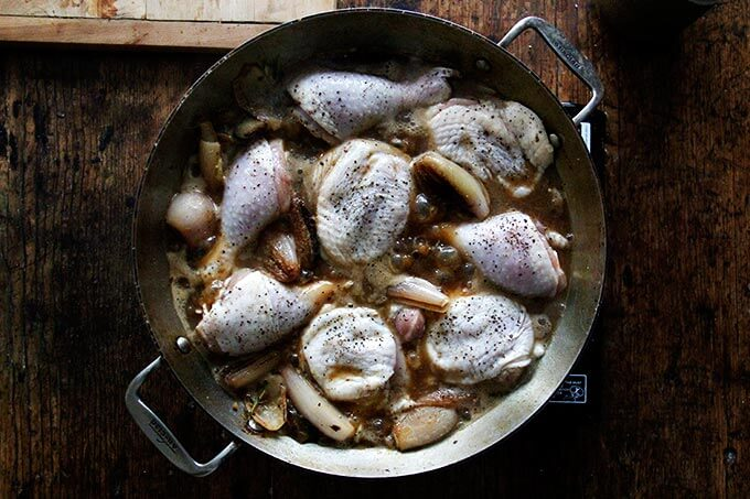 Chicken in a skillet with shallots.