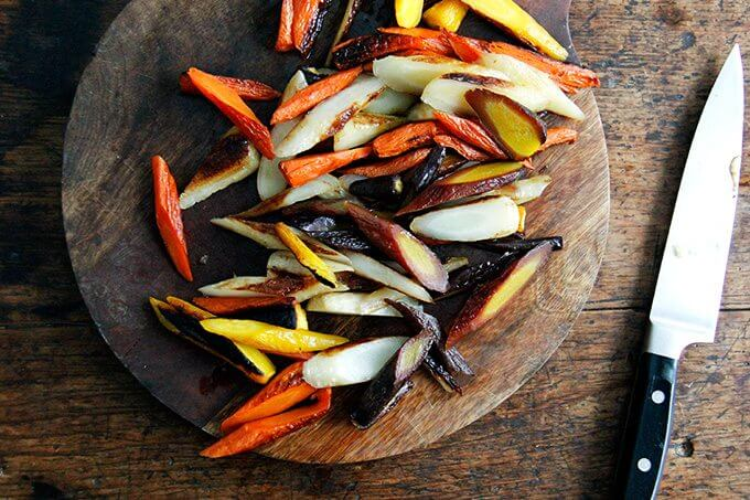 Sliced roasted carrots on a board.