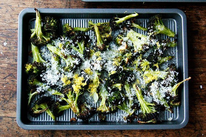 A sheet pan with roasted broccoli covered with parmesan and lemon.